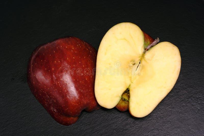 Rode gehakte appel op zwarte stock fotografie