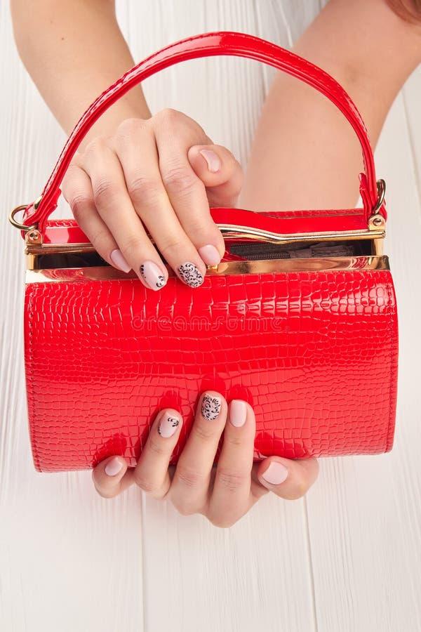 Rode gelakte zak in vrouwelijke handen stock afbeelding