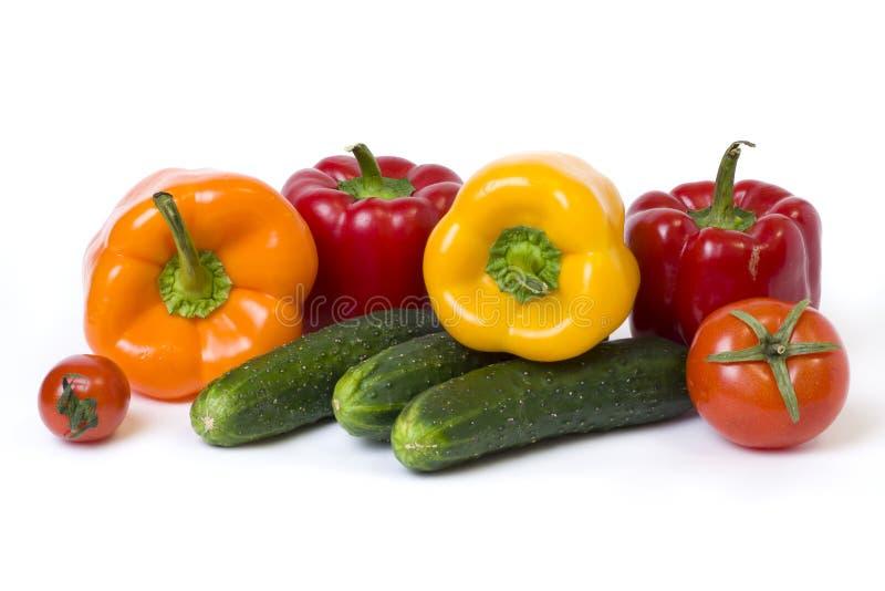 Rode gele en oranje peper met tomaten op een witte achtergrond Komkommers met kleurrijke peper in samenstelling op een witte back royalty-vrije stock afbeelding