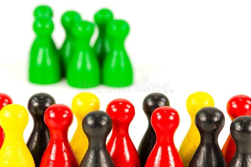 Rode, gele en zwarte halmakegels tegen groene halmakegels stock afbeelding