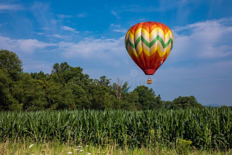 Rode, Gele, Oranje, Groene, en Witte Traan Gevormde Hete Luchtballon over Graangebied op Sunny Day met Bomen en Bewolkte Blauwe H royalty-vrije stock afbeeldingen