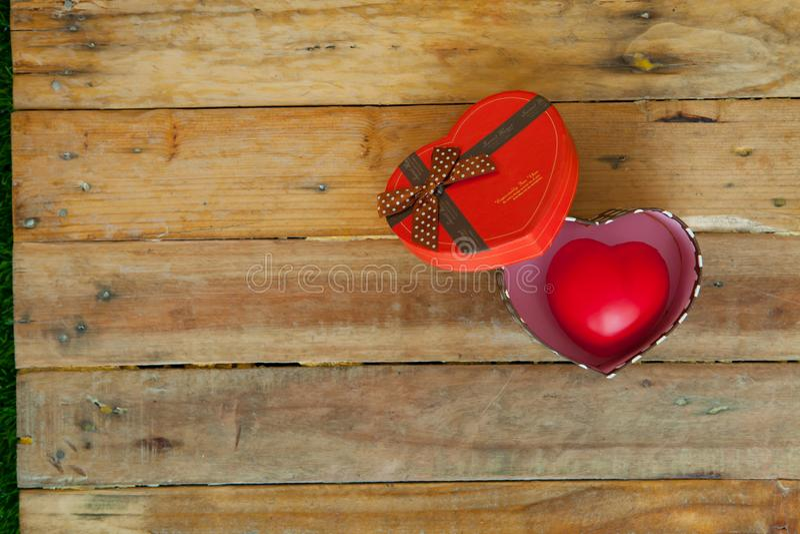 Rode giftdoos en rood lint en minihart binnen op hout backgr stock afbeeldingen