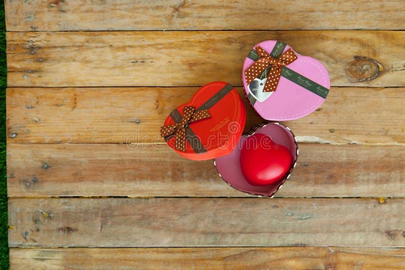Rode giftdoos en rood lint en minihart binnen op hout backgr stock afbeelding