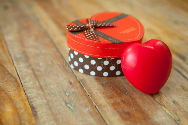 Rode giftdoos en rood lint en minihart binnen op hout backgr royalty-vrije stock afbeeldingen