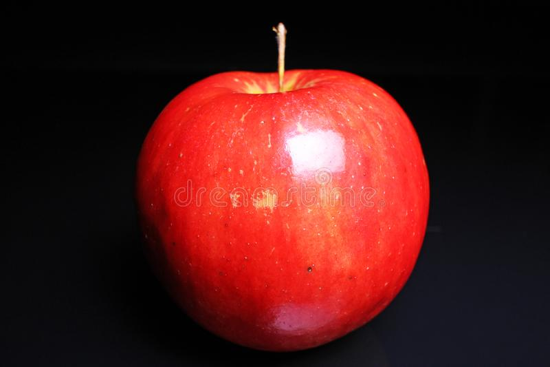 Rode glanzende gehele appel op zwarte weerspiegelende studioachtergrond Geïsoleerde zwarte glanzende spiegel weerspiegelde achter stock afbeeldingen