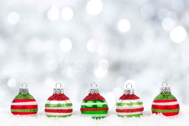 Rode, groene, witte Kerstmisornamenten in sneeuw met fonkelende achtergrond royalty-vrije stock afbeeldingen