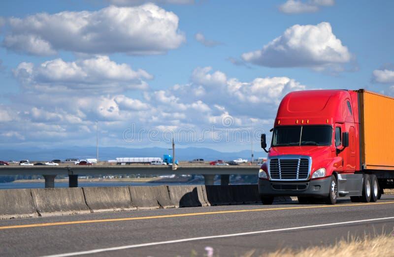 Rode grote installatie semi vrachtwagen die container op de weg met r vervoeren stock afbeelding