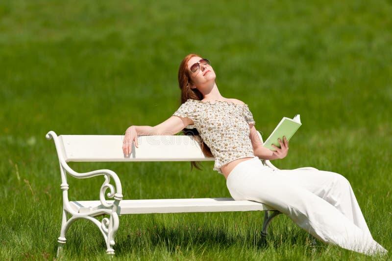Rode haarvrouw die van zon op witte bank geniet royalty-vrije stock foto