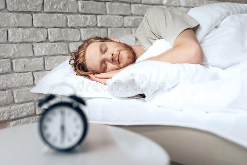 Rode haired jonge mensenslaap in slaapkamer royalty-vrije stock afbeeldingen