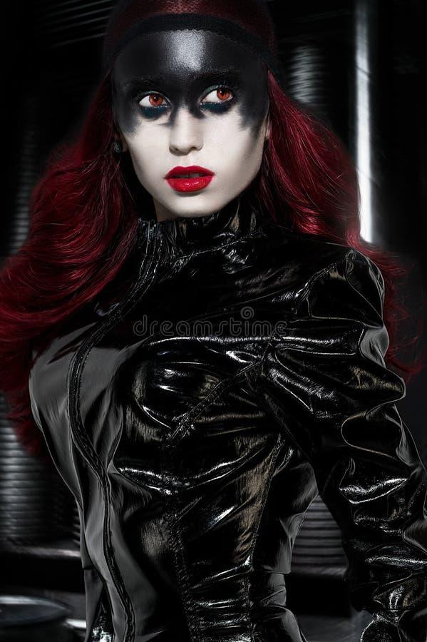 Rode haired vrouw met bizarre zwarte make-up stock foto's