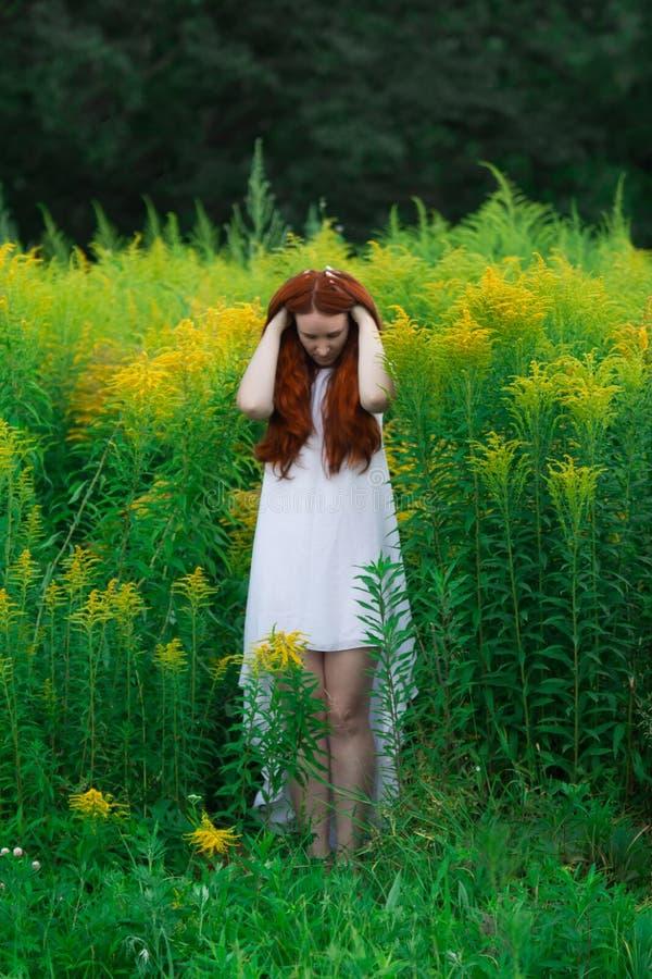 Rode haired vrouw met gele bloemen stock afbeeldingen