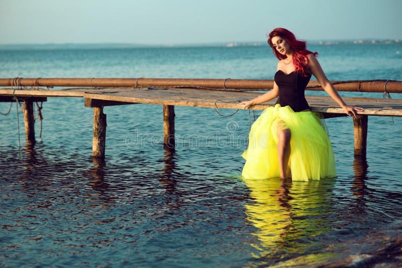 Rode haired vrouw in zwart korset en lange staart groene versluierende rok die zich in zeewater bevinden en op houten pijler leun royalty-vrije stock foto