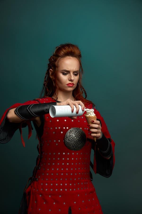 Rode haired vrouwelijke strijder die heerlijk roomijs eten stock fotografie