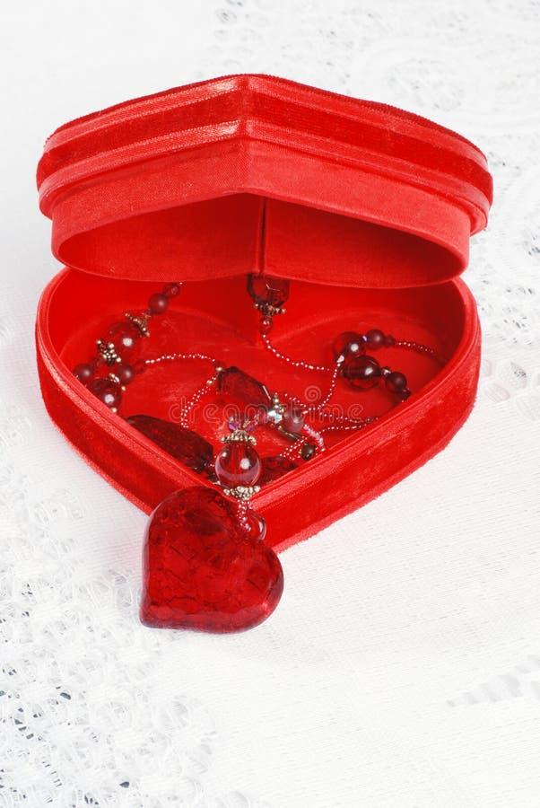 Rode halsband in de doos van hartjuwelen stock foto's