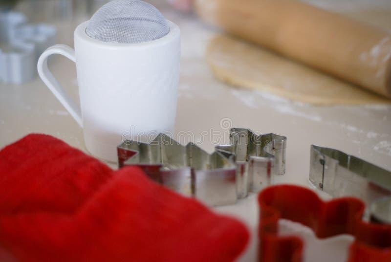 Rode handdoek, wit zeefje, rode en zilveren koekjessnijders, deegrol met deeg met lichte achtergrond royalty-vrije stock afbeeldingen