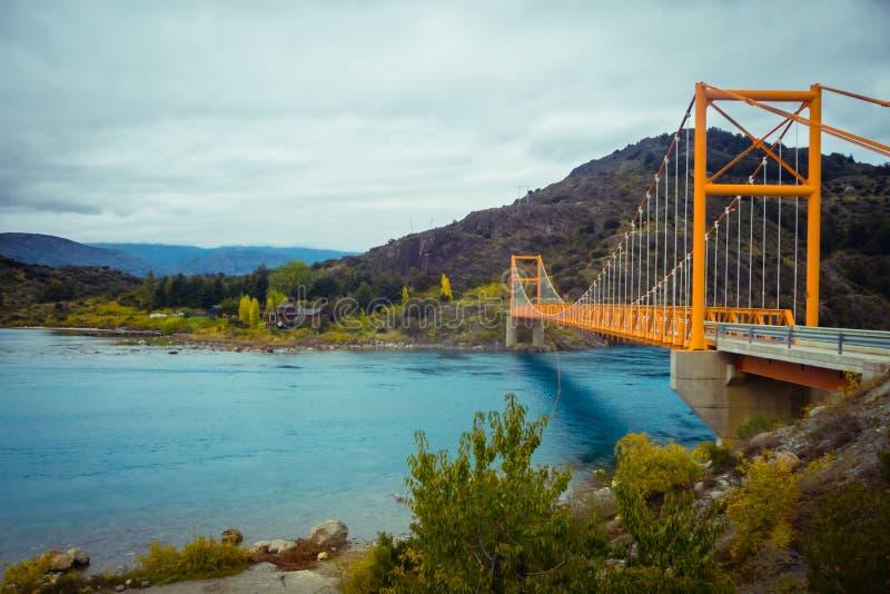 Rode hangbrug over de waterreproductie van Algemeen Carrera-Meer, dichtbij Meer Bertrand, Puerto Tranquilo, Chili Chico, Aysen, royalty-vrije stock afbeelding