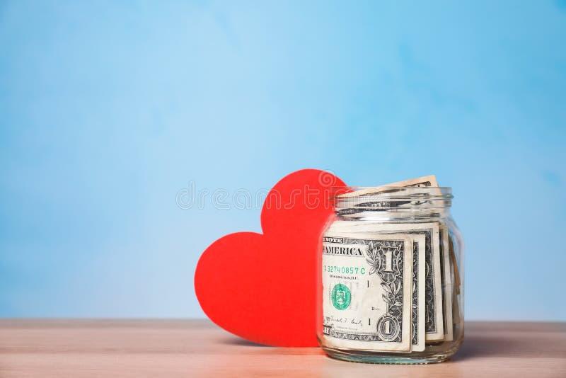 Rode hart en schenkingskruik met geld op lijst tegen kleurenachtergrond stock foto