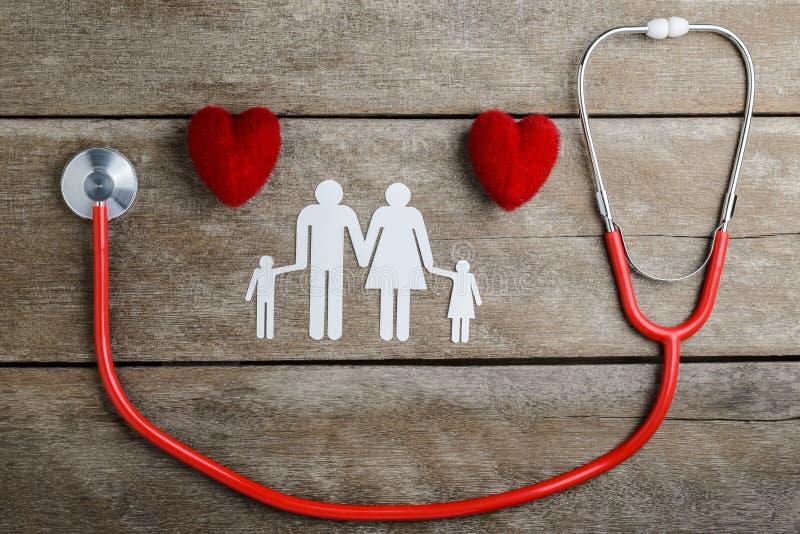 Rode hart, stethoscoop en document kettingsfamilie op houten lijst stock foto