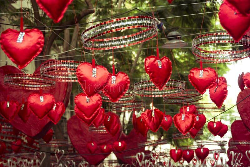 Rode harten die en zich in Gracia-district, Barcelona hangen bewegen stock foto's