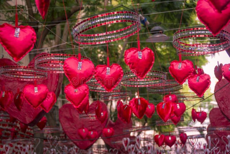 Rode harten die en zich in Gracia-district, Barcelona hangen bewegen stock afbeelding