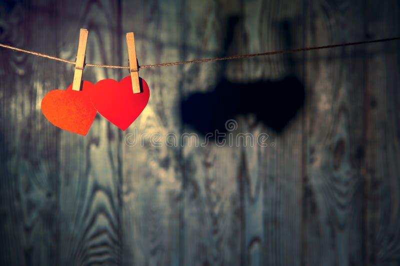 Rode harten met wasknijpers op linnenkabel stock afbeelding