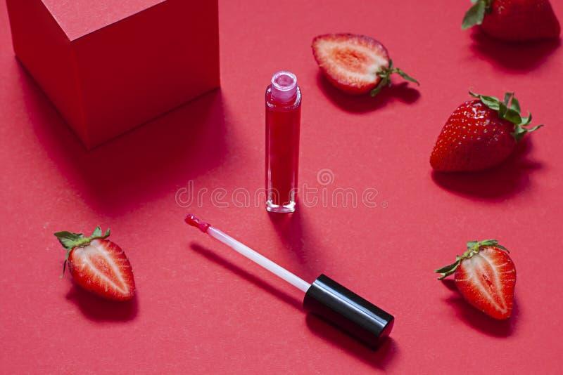 Rode het concepten dichte omhooggaand van de lipglossschoonheid met verse aardbeien royalty-vrije stock afbeelding