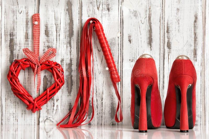 Rode het harthandcuffs van de schoenenzweep op een houten achtergrond royalty-vrije stock afbeeldingen