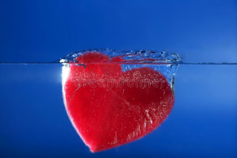 Rode het hartvorm die van het suikergoed in het blauwe water daalt royalty-vrije stock fotografie