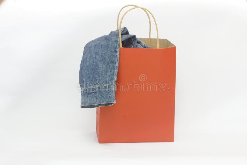 Rode het winkelen zak met doek daarin op geïsoleerde witte achtergrond stock foto's