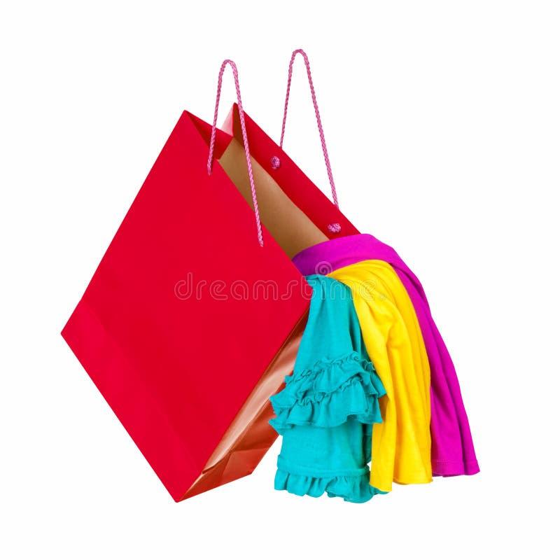 Rode het winkelen zak met kleurrijke kleren die in de lucht vallen Conce stock afbeeldingen