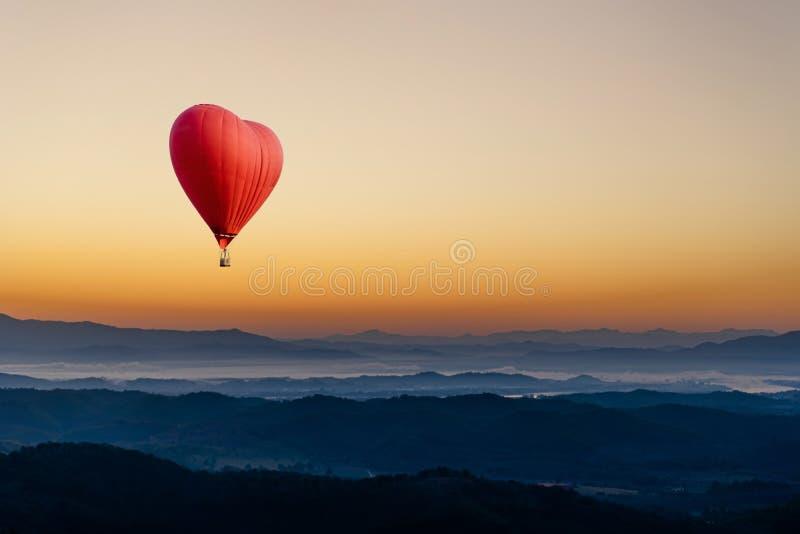 Rode hete luchtballon in de vorm van een hart dat over de berg vliegt stock afbeelding