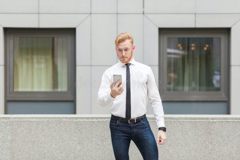 Rode hoofd jonge volwassen manager die slimme telefoon met geschokt gezicht bekijken stock afbeeldingen