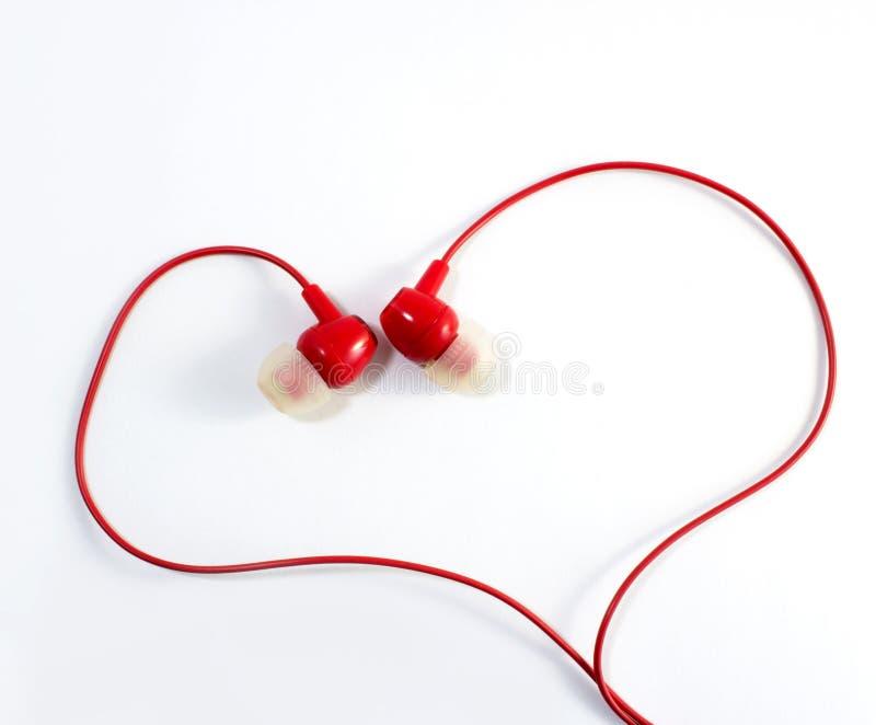 Rode hoofdtelefoons in hartvorm, liefde, muziek stock foto
