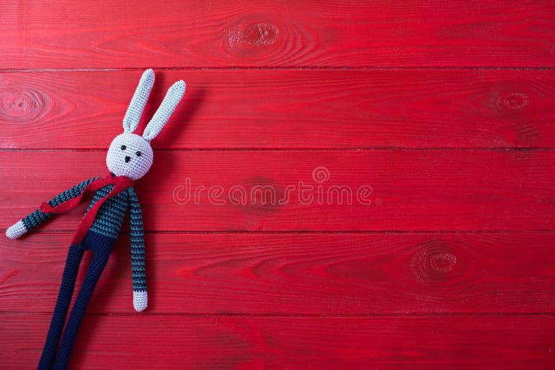 Rode houten achtergrond voor uw ontwerp Een stuk speelgoed is een haas in de techniek van amigurumi wordt gebreid die royalty-vrije stock foto's