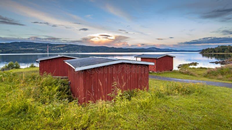 Rode houten cabines op waterkant van meer in Noorwegen stock foto's