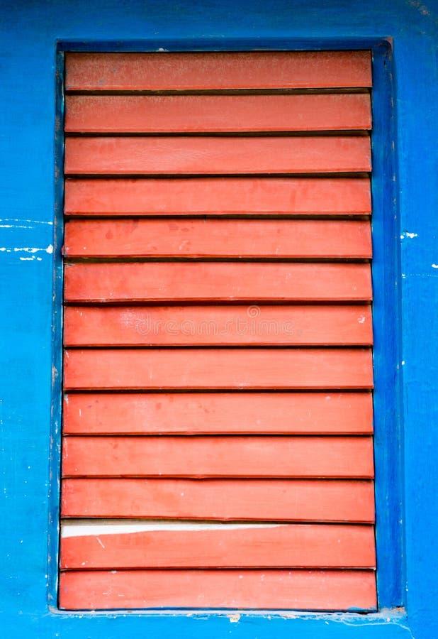 Rode houten die blinden op venster op blauwe muur worden gesloten stock afbeelding