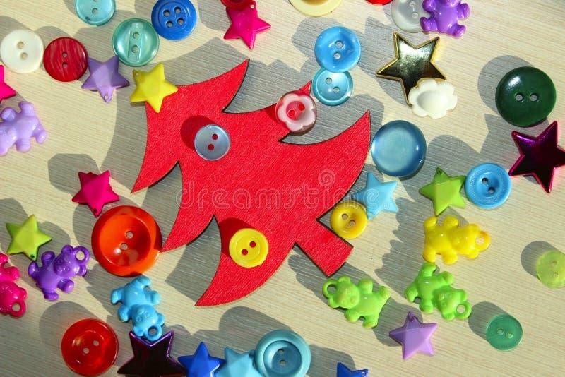 Rode Houten Kerstboom en Kleurrijke knopen over Houten Achtergrond met Heel wat Exemplaarruimte voor Tekst royalty-vrije stock afbeeldingen