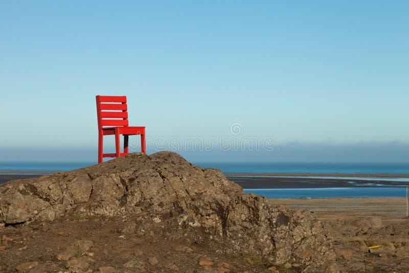 Rode houten stoel op een leeg steenachtig landschap in IJsland stock afbeelding