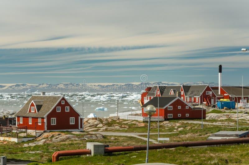 Rode huizen in de stad Ilulissat, mening over ijsberg in de Disko-baai aan Qeqertarsuaq-eiland en de gletsjer op de achtergrond, stock foto's