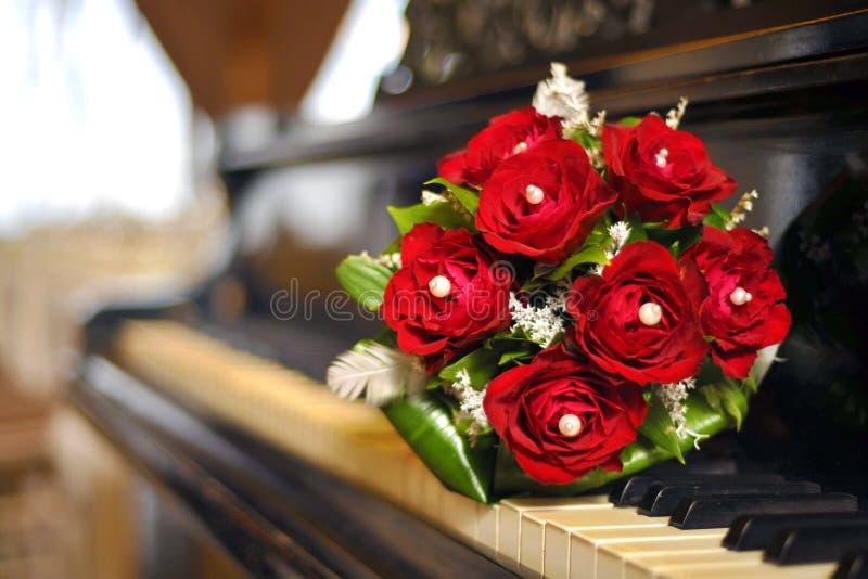Rode huwelijksbloemen op de piano royalty-vrije stock afbeeldingen