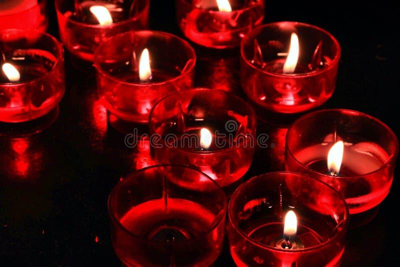 Rode Kaarsen die door gebeden in een kerk worden aangestoken royalty-vrije stock foto