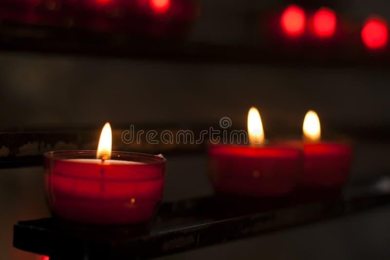 Rode kaarsen in een kerk stock afbeeldingen