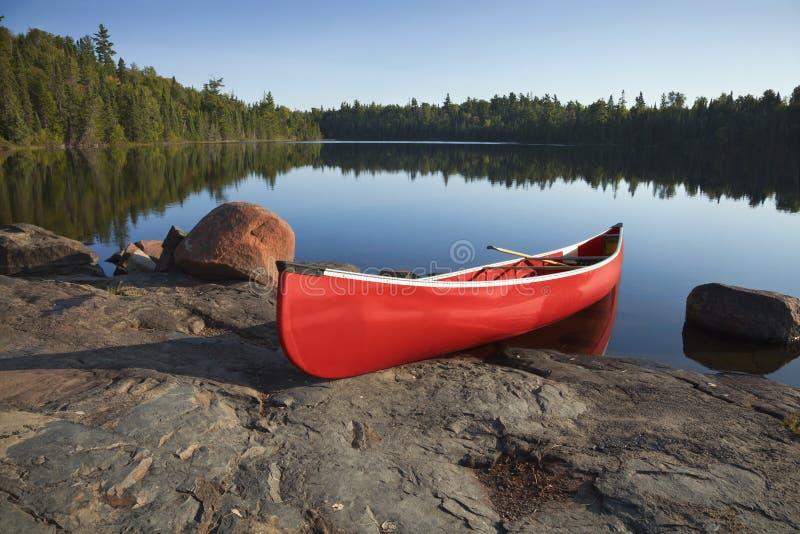 Rode Kano op Rocky Shore van Kalm Meer met Pijnboombomen royalty-vrije stock afbeeldingen