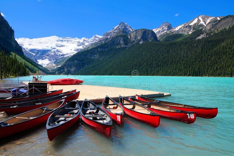 Rode kano's in de blauwe wateren van Meer Louise, Banff, Canada royalty-vrije stock foto