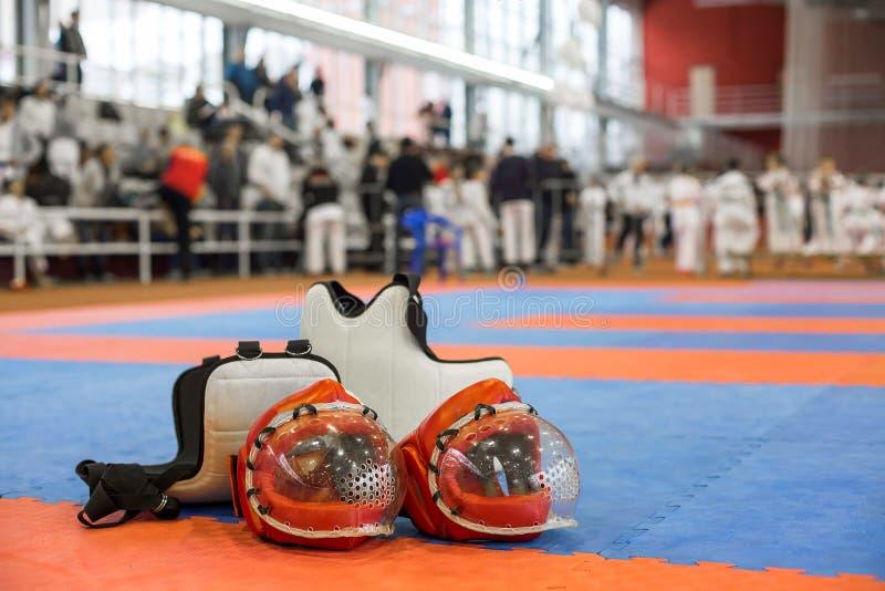 Rode karate twee het vechten helm met duidelijke plastic maskers en twee lichaams beschermende vesten op de rode blauwe vloer royalty-vrije stock foto's