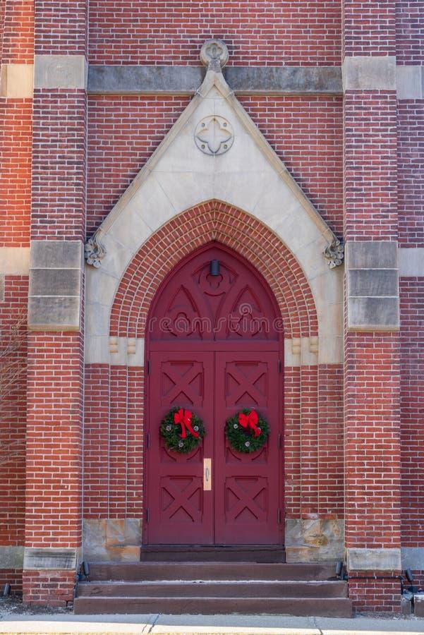 Rode kerkdeuren met Kerstmiskronen royalty-vrije stock fotografie