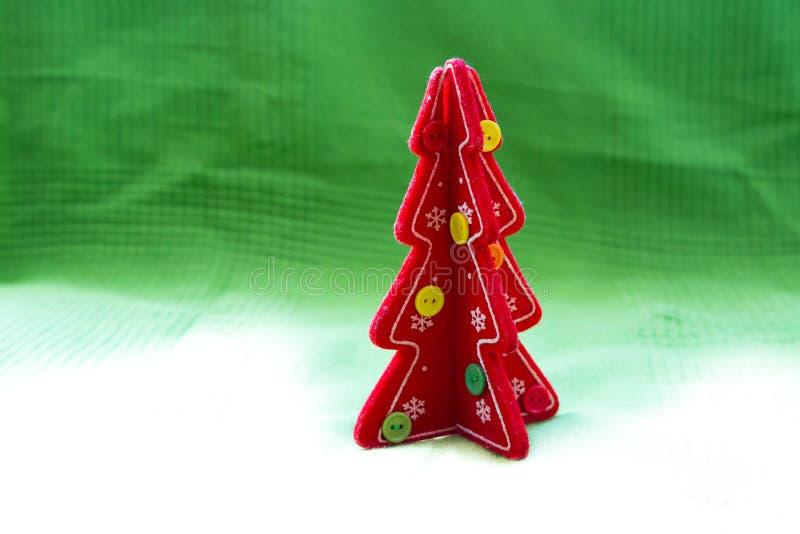 Rode Kerstboom op een wit aan groene canvasachtergrond stock afbeelding