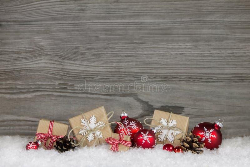 Rode Kerstmis stelt verpakt in natuurlijk document op oude houten gr. voor stock foto