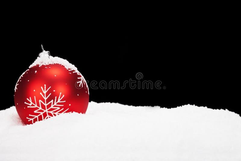 Rode Kerstmisbal in sneeuw royalty-vrije stock afbeeldingen