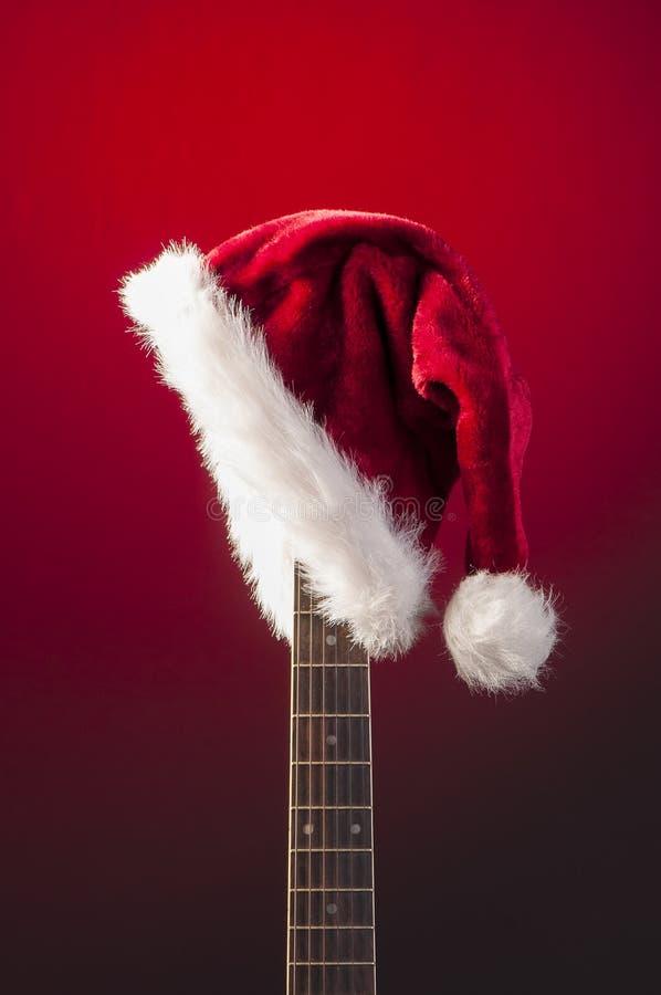 Rode Kerstmishoed op gitaar stock fotografie